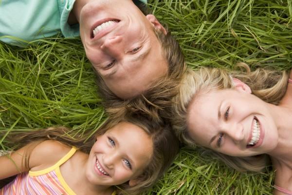 familie liegend im gras laechelnd