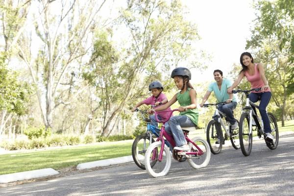 junge familie reitfahrraeder im park