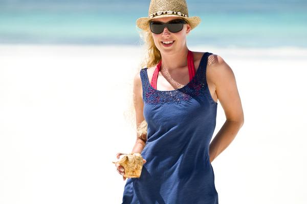 junge frau mit kokosnussdrink am strand