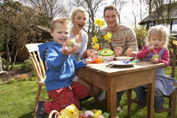 familie dekorieren ostereier auf tisch im