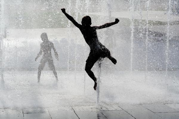 glueckliche nasse sommerkinder die im wasserbrunnen