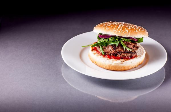 hamburger mit rucola auf grau oberflaeche