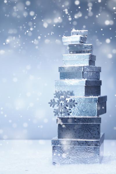 gestapelte weihnachtsgeschenke im winter schneefall