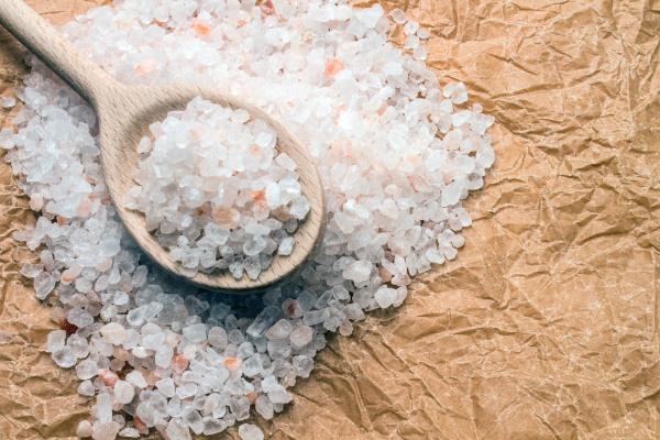 holzloeffel mit groben salz auf knitterpapier