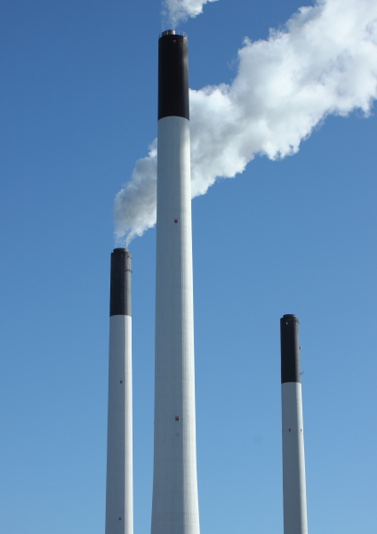 fabrikschornsteine in der energieanlage mit blauem