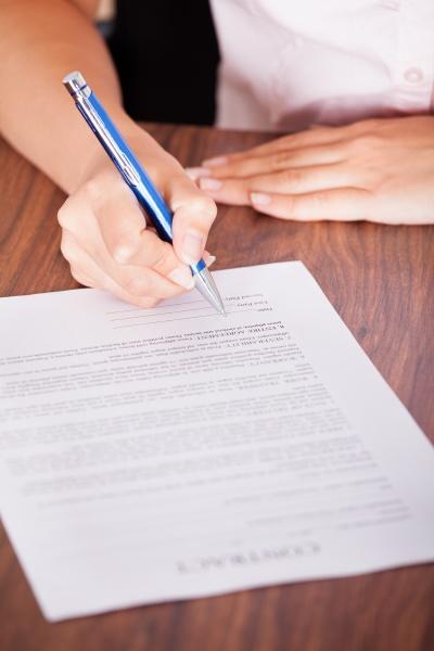 frau die das vertragspapier unterzeichnet