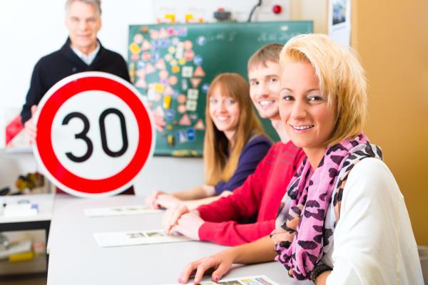 fahrlehrer mit seiner klasse mit fahrschuelern