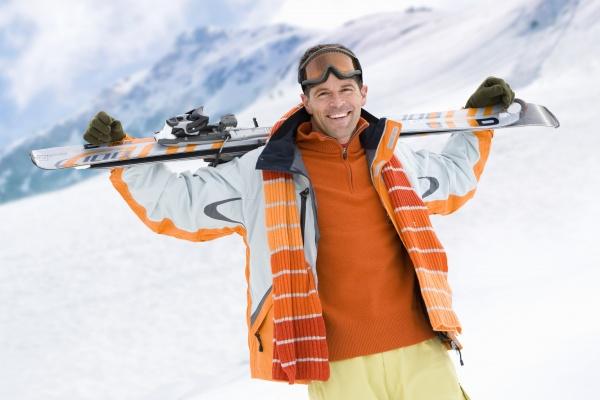 laechelnden mann mit skiern auf dem