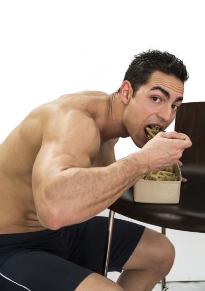 hungrig muskuloeser hemdsloser mann schluckt lebensmittel