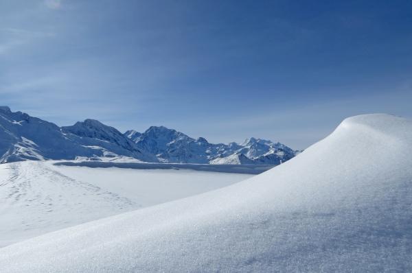 tief verschneites hochgebirge mit blauem himmel