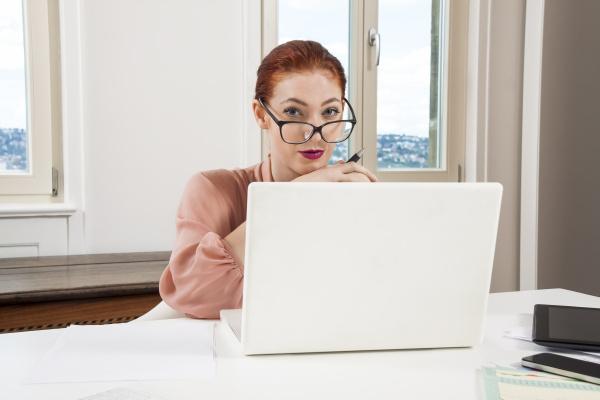 junge geschaeftsfrau liest statistiken am schreibtisch