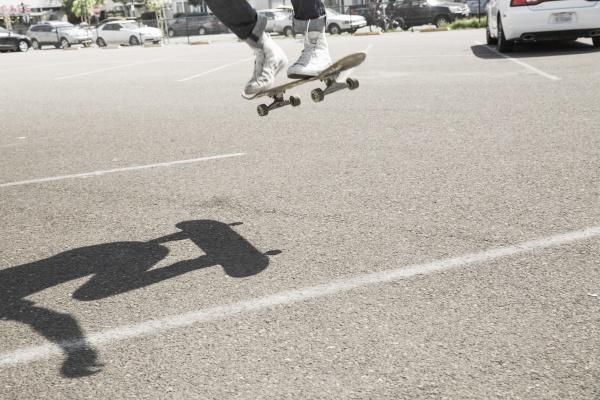 junger mann skateboarding auf einem parkplatz