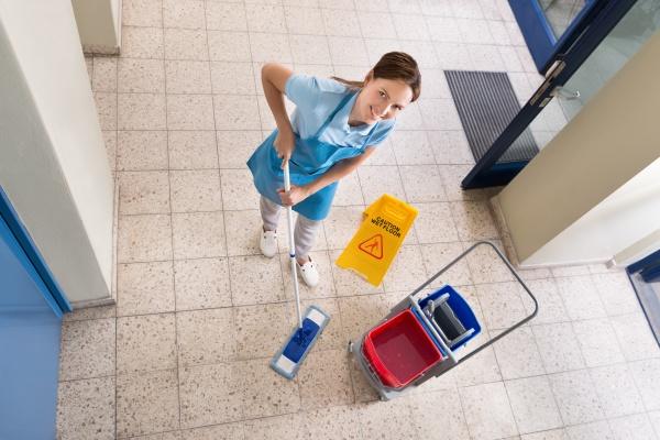 janitor halten mop mit reinigungsausruestungen und