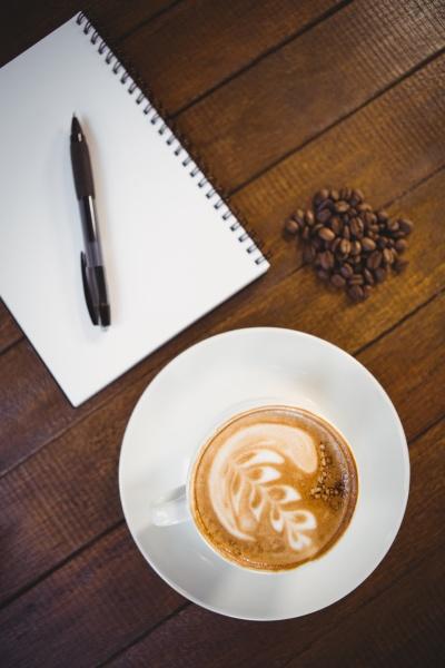 tasse cappuccino mit kaffeekunst und notizblock