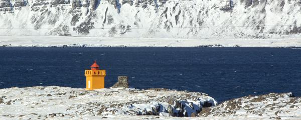 weitschusspanorama eines orangefarbenen leuchtturms island