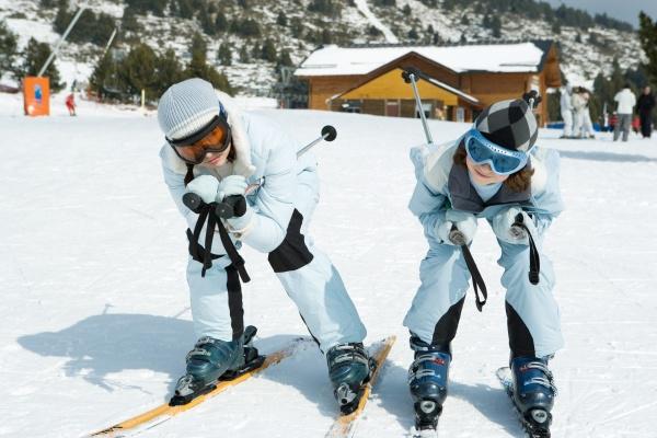 zwei junge skifahrer hockend zusammen blick