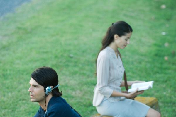menschen sitzen im park mann hoert