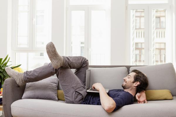 entspannter mann auf der couch liegen