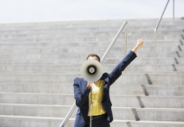 geschaeftsfrau mit megaphon auf staedtischen stufen