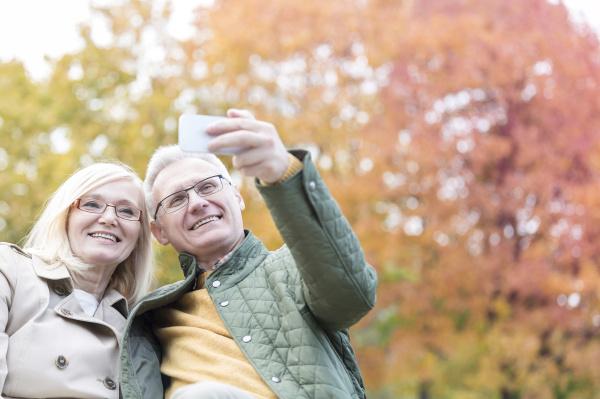 laechelnde aeltere paar selfie mit kamera