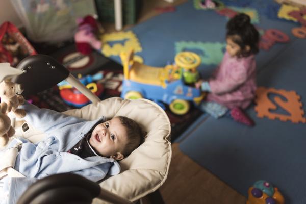 gluecklicher babyjunge der im babytraeger liegt