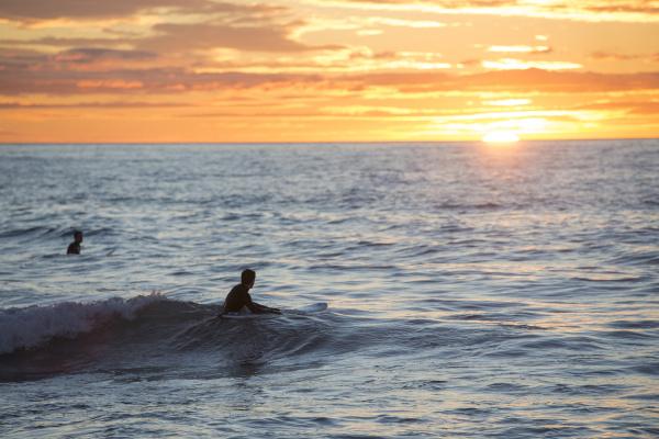 zwei surfer bei sonnenaufgang