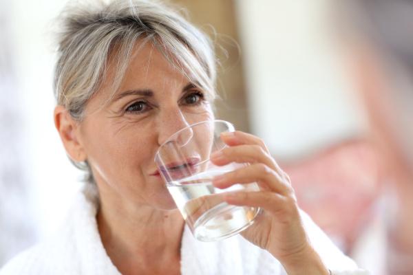 aeltere frau trinkwasser am morgen