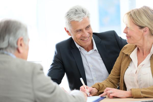 senior paar sitzung immobilienmakler fuer investitionen