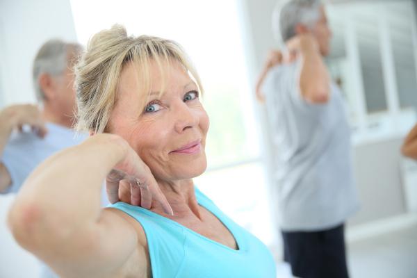 senioren die sich im fitnessraum ausdehnen