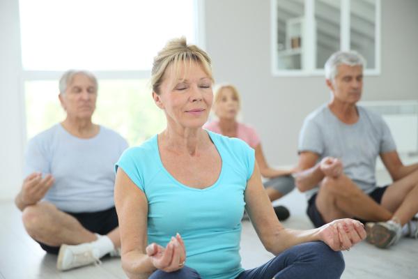 gruppe aeltere leute die yoga uebungen