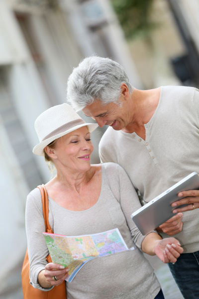 aeltere touristen in strasse mit karte