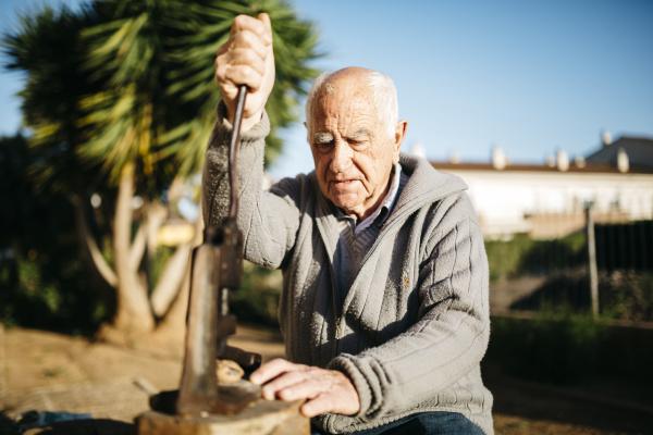 senior mann mit einem alten werkzeug