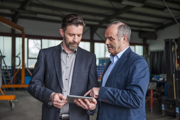 ingenieure mit digitalem tablet in werkstatt