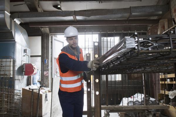 fabrikarbeiter waehlt stahlgitter in betonbewehrungsfabrik
