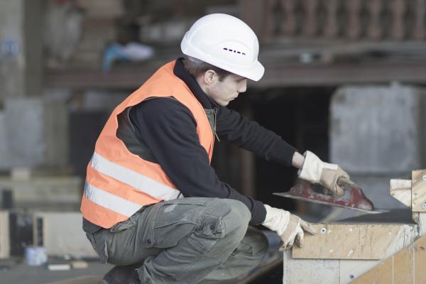 fabrikarbeiter mit fertigkelle auf beton in