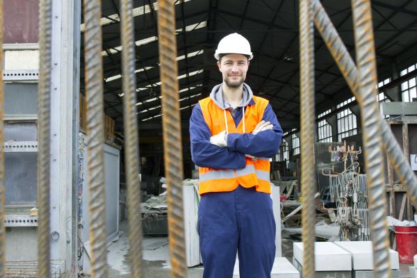 portraet eines fabrikarbeiters vor der betonbewehrungsfabrik