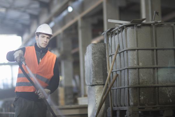 fabrikarbeiter putzen mit wasserschlauch in betonbewehrungsfabrik