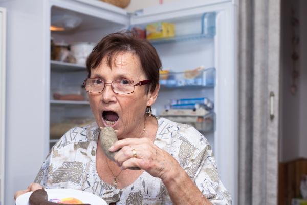 seniorenfrau isst schweinefleisch wurst