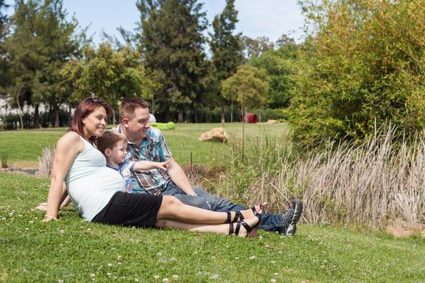junge schwangere familie entspannen im park
