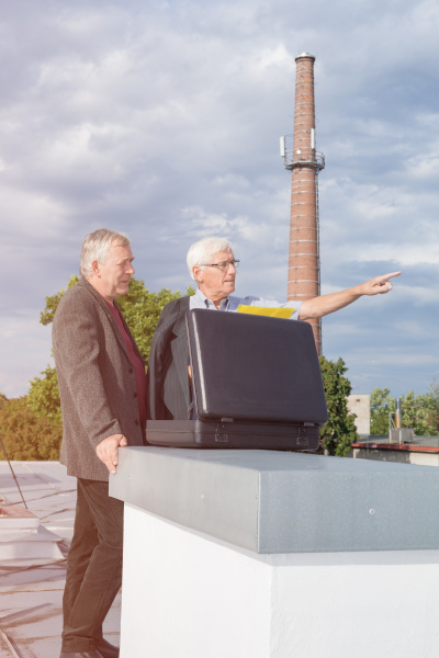 hochrangige geschaeftsleute diskutieren auf dem dach
