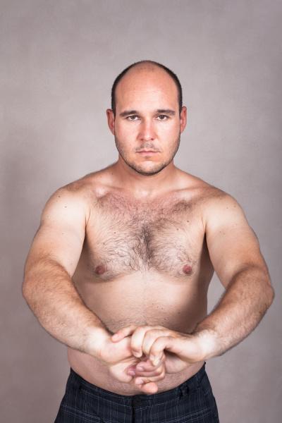 serious shirtless man zeigt seinen starken