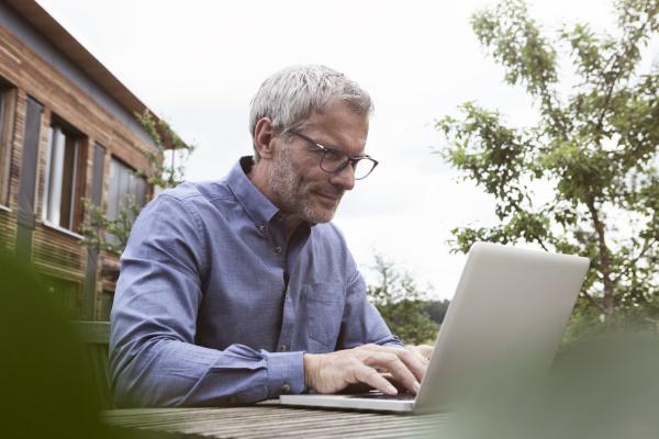 aeltere menschen laptop auf gartentisch mit