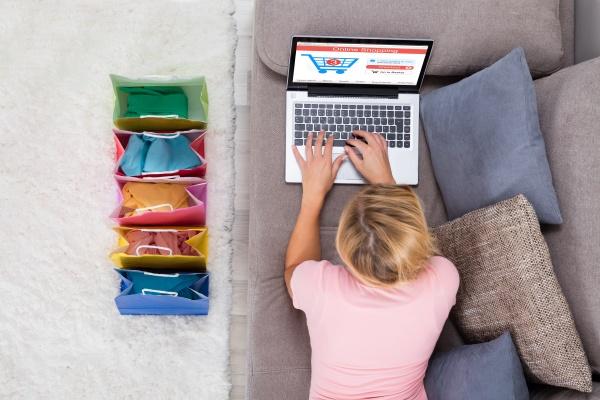 frau liegt auf sofa mit laptop