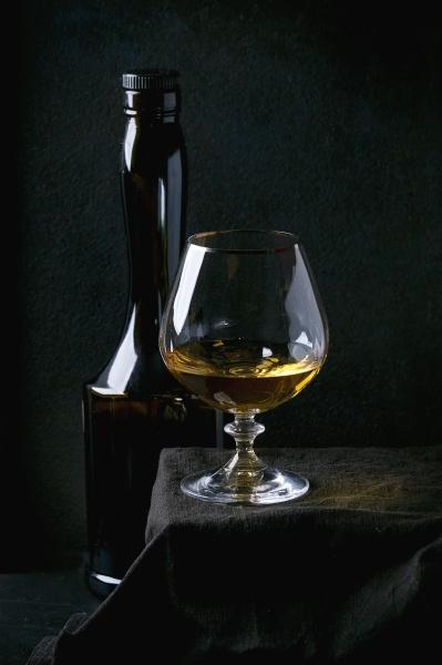flasche und glas franzoesischer apfelcalvados auf