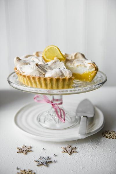 zitronenmensue kuchen auf einem glaesernen tortenstand