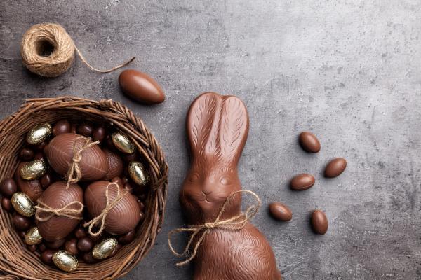 schokoladen osterhase und eier auf hoelzernem