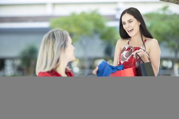 zwei glueckliche frauen mit einkaufstueten