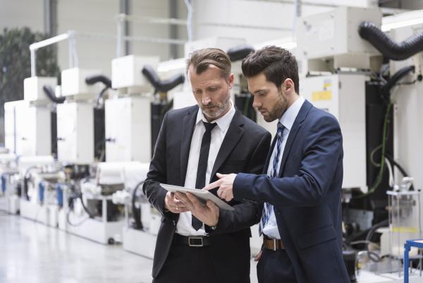 zwei geschaeftsmaenner die tablette im fabrikshopboden