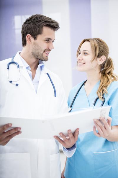 zwei laechelnde doktoren die ordner halten