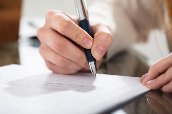 geschaeftsperson die dokument mit stift unterzeichnet